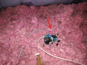 Open junction box inside an attic