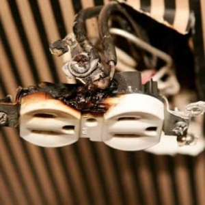 Inside of a burnt electrical outlet with visible aluminum wiring